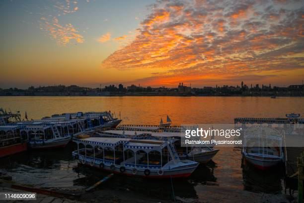 river nile with traditional boats at sunrise on the river nile, luxor, egypt - aswan stock pictures, royalty-free photos & images