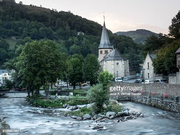 River of high mountain that an ancient people crosses with a church.  France ,  Pyrenees, (Arreau)