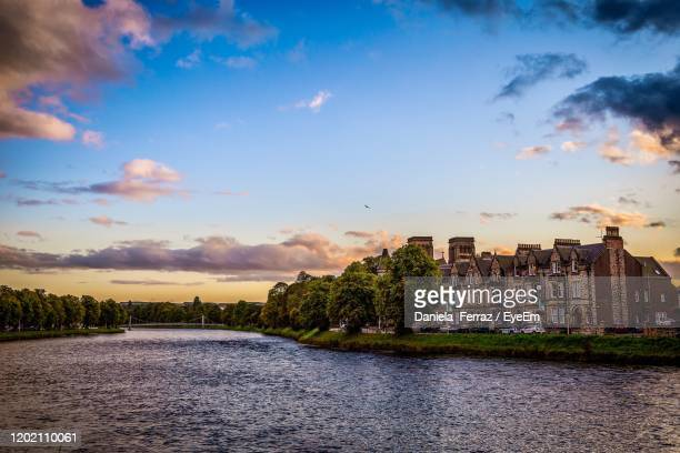 river passing through buildings against sky during sunset - inverness scotland stock pictures, royalty-free photos & images