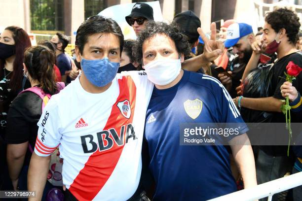 River Plate and Boca Juniors fan pose for a picture together as they queue in line to pay tribute to Diego Maradona in the goverment palace on...