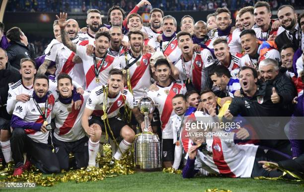 TOPSHOT River Plate celebrates with the trophy after winning the second leg match of the allArgentine Copa Libertadores final against Boca Juniors at...