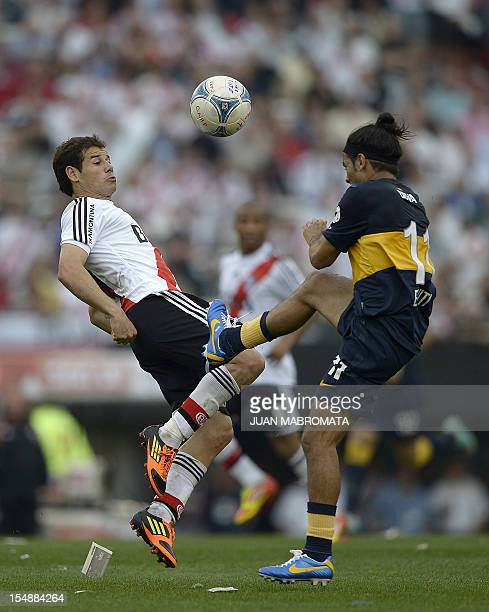 River Plate forward Rodrigo Mora vies for the ball with Boca Juniors midfielder Walter Erviti during their Argentine First Division football match at...