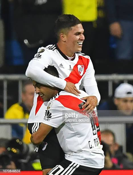 River Plate's Colombian Juan Fernando Quintero celebrates with teammate Gonzalo Martinez after scoring against Boca Juniors during the second leg...