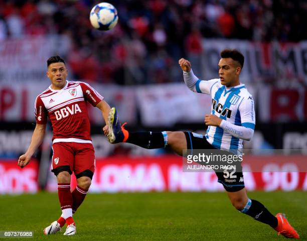 River Plate's defender Jorge Moreira vies for the ball with Racing's forward Lautaro Martinez during their Argentina First Divsion football match at...