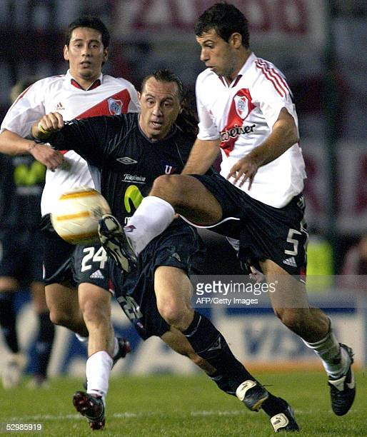 River Plate's Javier Mascherano vies with Liga Deportiva Universitaria's Alex Aguinaga while teammate Rubens Sambueza looks 26 May 2005 during their...