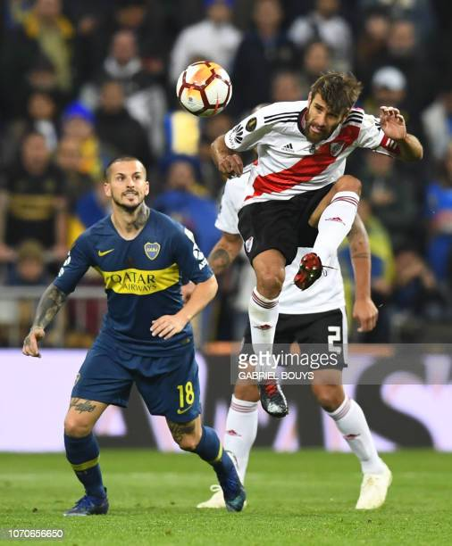 River Plate's Leonardo Ponzio heads the ball as Boca Juniors' Dario Benedetto looks on during the second leg match of their allArgentine Copa...