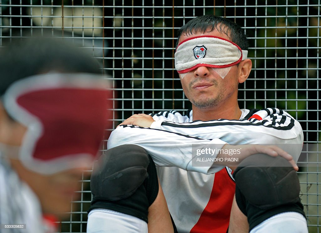 River Plate's Marcelo Panisa rests after the end of half time during a blind football match of the Argentine FaDeC (Argentine Federation of Sports for the Blind) championship in Buenos Aires on May 21, 2106. Boca Juniors won 1-0. Five-a-side blind football is contested by teams made up of four visually impaired outfield players wearing blindfolds with a goalkeeper who may be fully sighted. The football they play with contains ball bearings to produce a noise when it moves. / AFP / ALEJANDRO