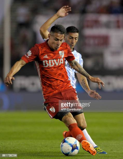 River Plate's midfielder Carlos Auzqui vies for the ball with Atletico Tucuman's midfielder Guillermo Acosta during their Argentina First Division...
