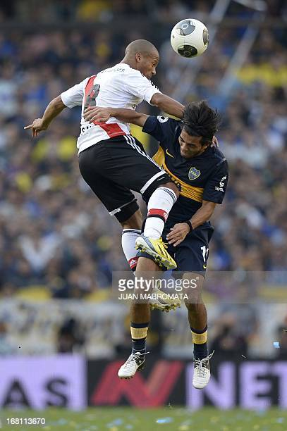River Plate's midfielder Carlos Sanchez and Boca Juniors' midfielder Walter Erviti jump for the ball during their Argentine first division football...