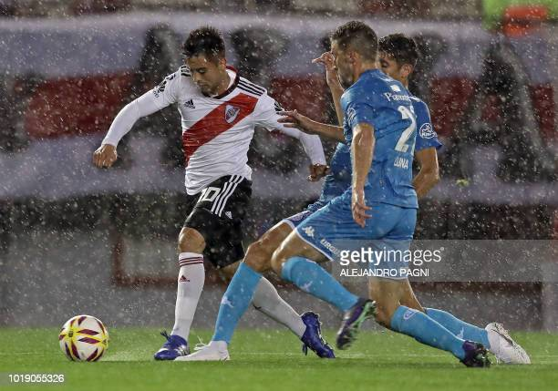 River Plate's midfielder Gonzalo Martinez controls the ball past Belgrano's midfielder Gabriel Alanis and defender Sebastian Luna during their...