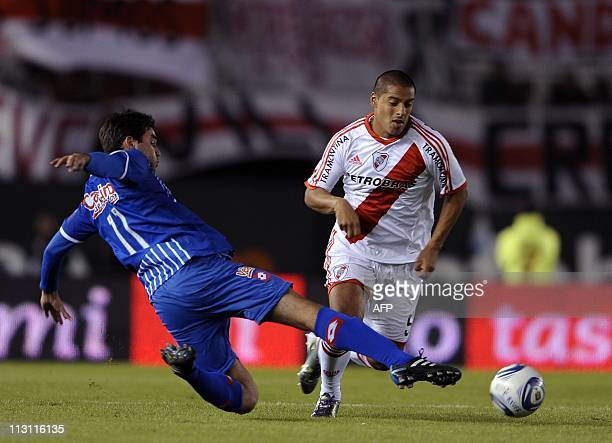 River Plate's midfielder Walter Acevedo vies for the ball with Godoy Cruz's forward Alvaro Navarro during the Argentina First Division football match...