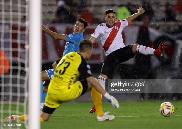 River Plate's Paraguayan defender Jorge Moreira eludes Belgrano's midfielder Gabriel Alanis and shots the ball against goalkeeper Cesar Rigamonti...