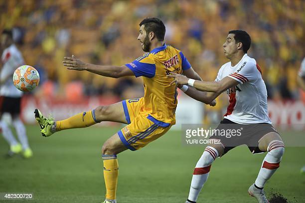 River Plate's Ramiro Funes vies for the ball with Tigres's Andre Gignac during their Copa Libertadores final match first leg against Tigres at the...