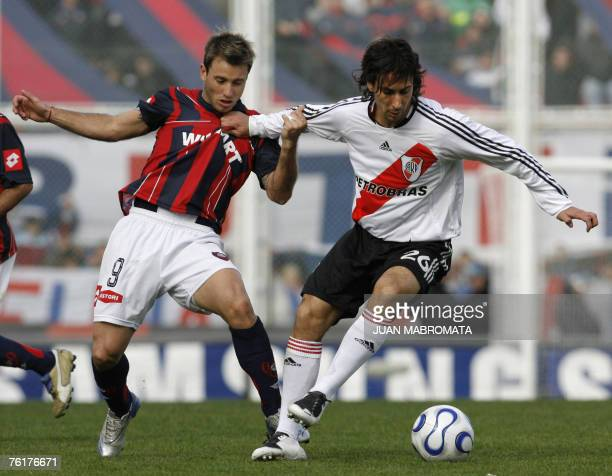 River Plate's Rene Lima vies for the ball with San Lorenzo's Gaston Fernandez during their Argentine First division soccer match at San Lorenzo...