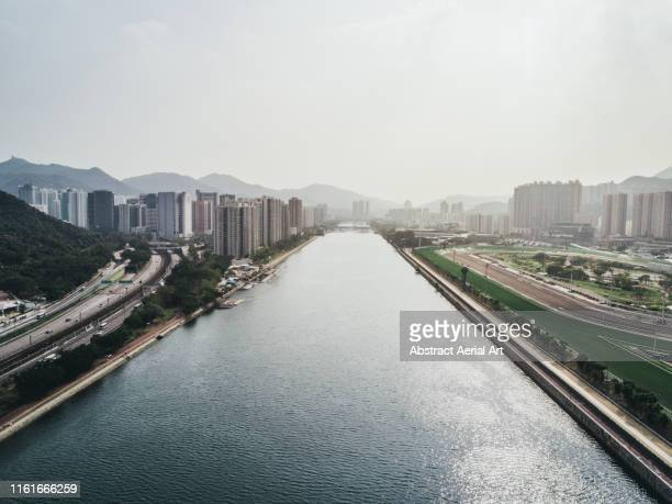 river splitting cityscape, hong kong - canal stock pictures, royalty-free photos & images