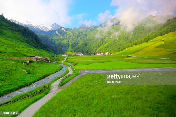 River stream and Intertux - Majestic Zillertal, Tyrol Snowcapped mountain range panorama and Idyllic Tirol valley meadows,  Austria