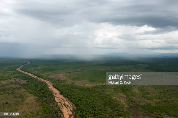 river system traversing savanna-woodland, evidence of clearing and cultivation, rain showers in the summertime, benoue-boubandjida, northern cameroon - kamerun stock-fotos und bilder