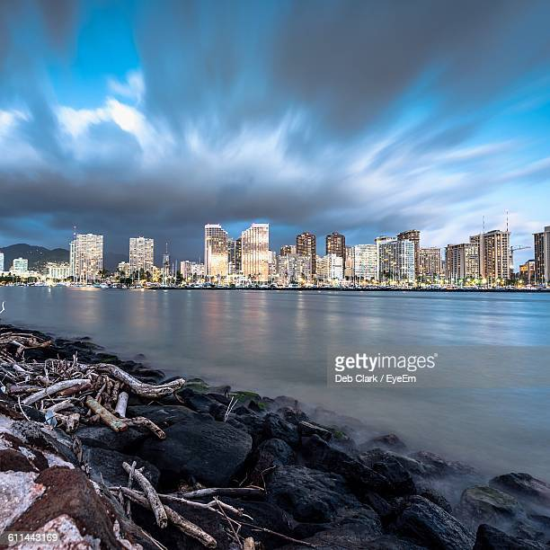 river with buildings against clouds - san leandro stock photos and pictures