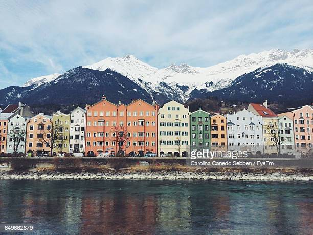 River With Buildings Against Snowed Mountains