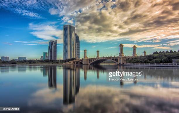 river with buildings in background - putrajaya stock photos and pictures