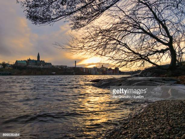 river with city in background at sunset - per grunditz stock pictures, royalty-free photos & images