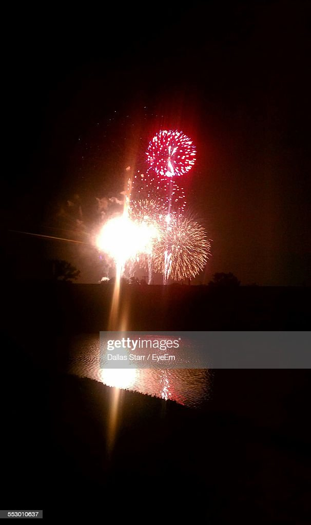 river with illuminated fire crackers in background at night stock photo