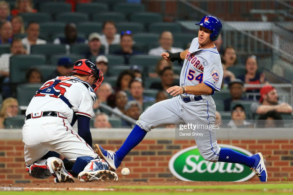 T.J. Rivera #54 of the New York Mets slides into home to score before the tag by Tyler Flowers #25 of the Atlanta Braves during the fifth inning at SunTrust Park on May 3, 2017 in Atlanta, Georgia.