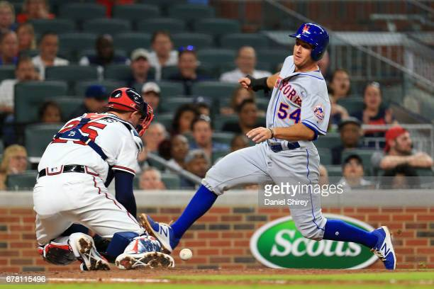 Rivera of the New York Mets slides into home to score before the tag by Tyler Flowers of the Atlanta Braves during the fifth inning at SunTrust Park...