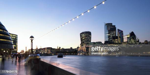 riverbank and the city skyline of london illuminated at dusk - urban road stock pictures, royalty-free photos & images