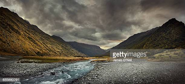 Riverbed in a valley with dramatic sky