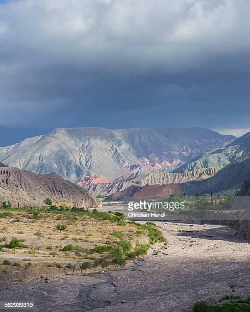 riverbed of the purmamarca and cerro de los siete colores or hill of seven colors in purmamarca, jujuy province, argentina - cerro de los siete colores foto e immagini stock