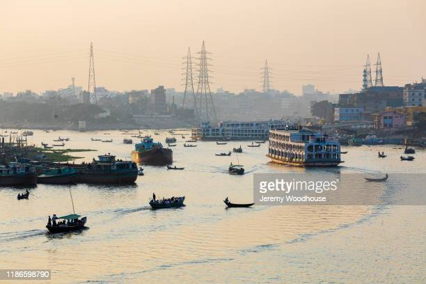 a riverboat heads north up the buriganga river - capital cities stock pictures, royalty-free photos & images