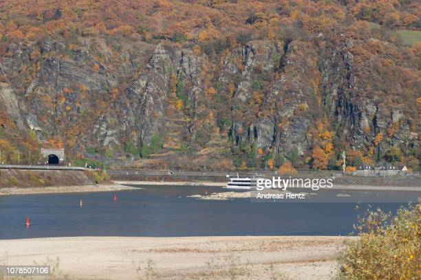 A riverboat passes banks and the low water in the River Rhine on November 13 2018 in Oberwesel Germany Summer heat wave in Germany as well...