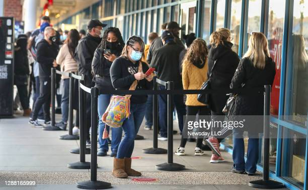 Black Friday shoppers line up outside the Michael Kors store at the Tanger outlet in Riverhead, New York at 6 a.m. On November 27, 2020.