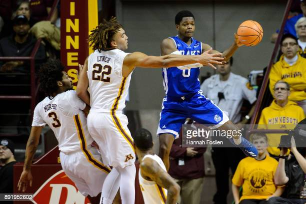 J Rivers of the Drake Bulldogs passes the ball away from Jordan Murphy and Reggie Lynch of the Minnesota Golden Gophers during the game on December...