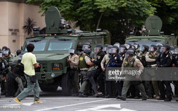 Riverside County Sheriffs and Riverside Police with armored vehicles advance on demonstrators who refused to disperse after curfew during a protest...