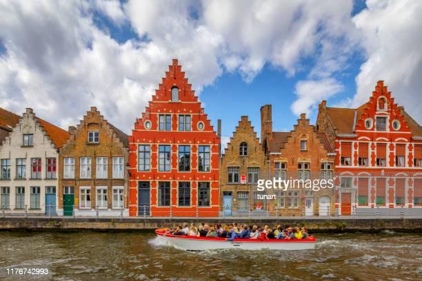 ベルギー、ブルージュのツアーボートでリバーサイドの家と観光客 - 運河 ストックフォトと画像
