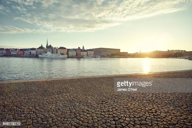 Riverside paving with distant buildings in the city at sunset, Stockholm, Sweden