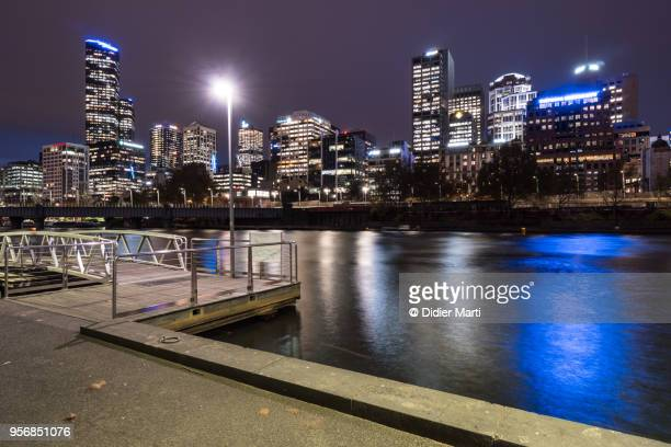 Riverside promenade along the Yarra river at night with the skyline in Melbourne in Australia