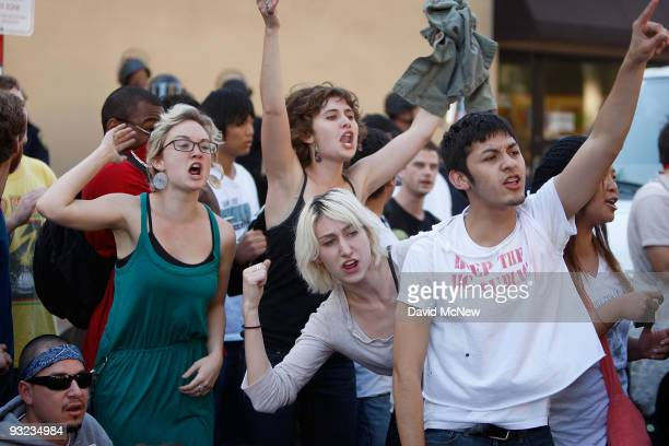 Riverside student Andrew Ojeda and other University of California Los Angeles students and supporters chant as they blockade a van trying to leave...