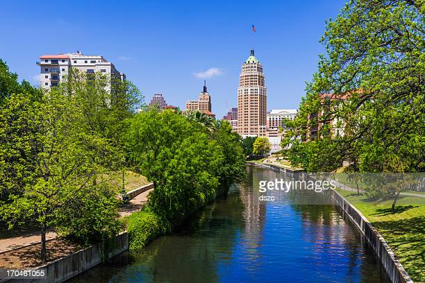 riverwalk san antonio texas skyline, park walkway along scenic canal - san antonio texas stock photos and pictures