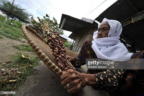 RIVETIn this photo taken December 3 2009 an Indonesian grandmother takes out the dirt from freshly harvested onions in Lampuuk village in Banda Aceh...