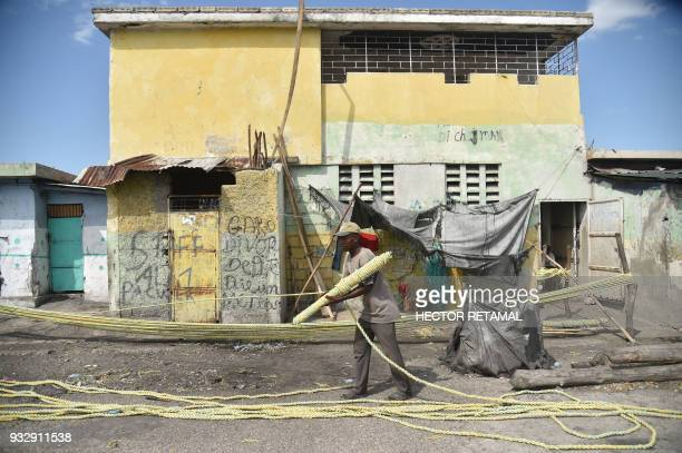 Rivien makes a plastic rope near the wharf of Cite Soleil in the commune of Cite Soleil PortauPrince on March 14 2018 to give it to fishermen in the...