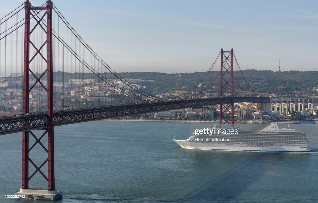 MS Riviera, from Oceania Cruises, sails under 25 de Abril bridge on the Tagus River, while leaving port on September 14, 2018 in Lisbon, Portugal. Lisbon harbor is one of the largest and most important ports in Europe and a hub for cruise shipping. The city hosts on 19 - 20 September Seatrade Cruise Med 2018 Conference, the cruise industrys leading trade event for the Mediterranean region and its adjoining seas.