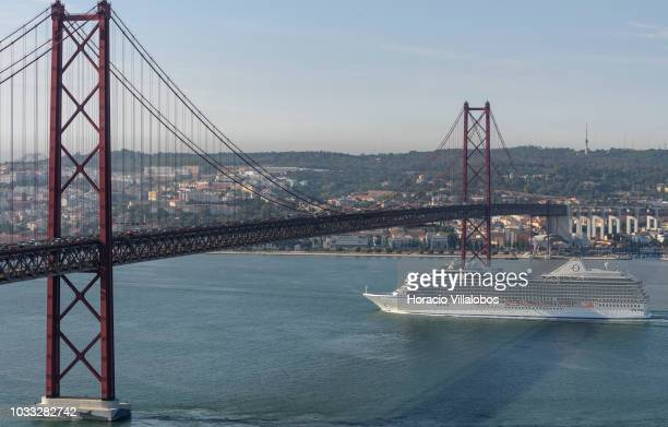 Riviera, from Oceania Cruises, sails under 25 de Abril bridge on the Tagus River, while leaving port on September 14, 2018 in Lisbon, Portugal....