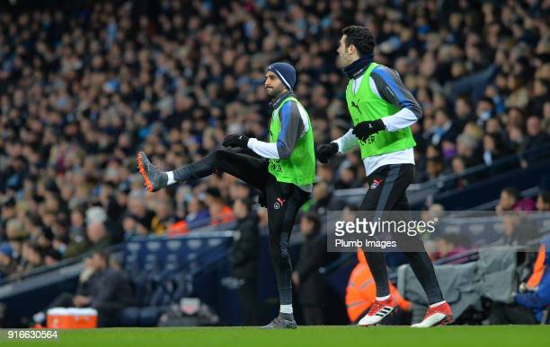 Riyad Mahrez and Vicente Iborra of Leicester City warm up from the bench during the Premier League match between Manchester City and Leicester City...