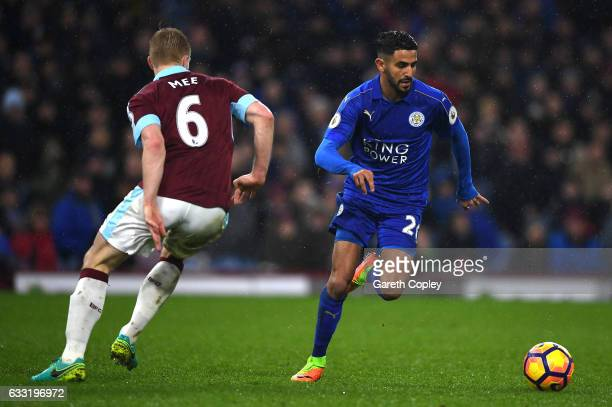 Riyad Mahrez of Leicester City and Ben Mee of Burnley compete for the ball during the Premier League match between Burnley and Leicester City at Turf...