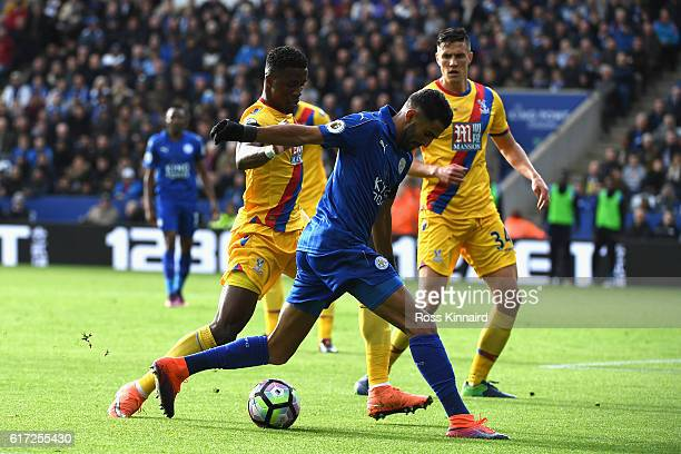 Riyad Mahrez of Leicester City and Wilfried Zaha of Crystal Palace compete for the ball during the Premier League match between Leicester City and...