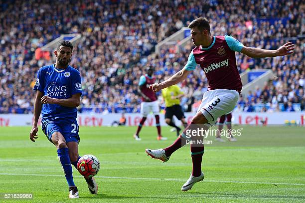 Riyad Mahrez of Leicester City blocks the clearance of Aaron Cresswell of West Ham United during the Barclays Premier League match between Leicester...
