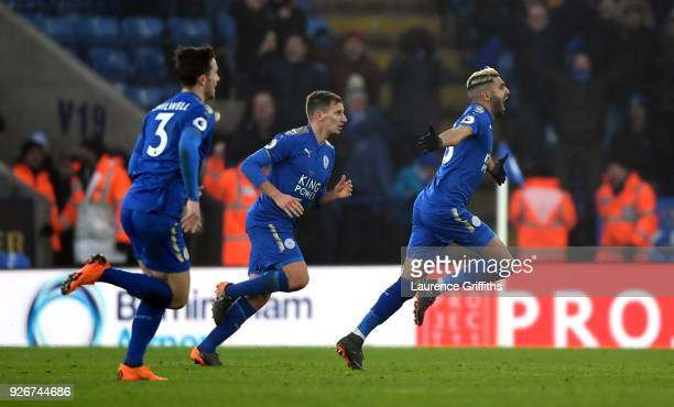 Riyad Mahrez of Leicester City celebrates scoring his side's first goal with team mates during the Premier League match between Leicester City and...